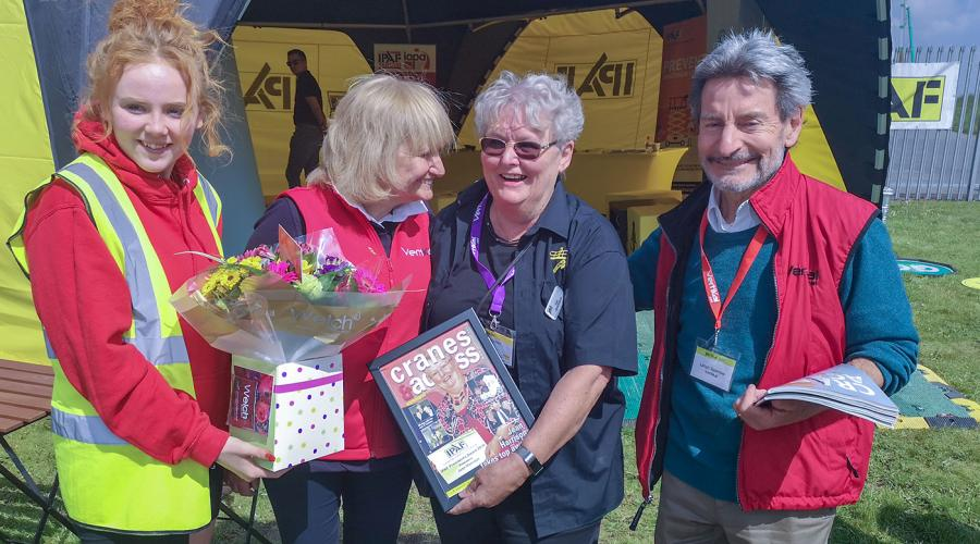 Jean Harrison at Vertikal Days 2019 at Donington Park, given a special send-off including a framed commemorative front cover of Cranes & Access magazine by event organisers.